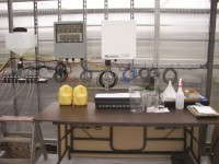 The pH controller (center), dilute acid tank and 8 solenoid valves with distribution lines (left) and datalogger (right)