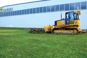 AgriNomix President Robert Lando mans a bulldozer to break ground on the new 15,0000-square-foot addition to AgriNomix